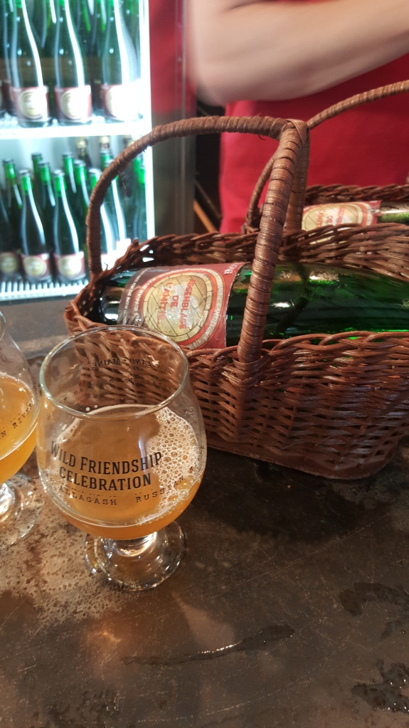 A bottle of the Belgian blend, called Assemblage de L'Amite, in a lambic basket and next to the commemorative Wild Friendship Blend glass with the beer